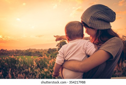 Young mother standing near a river & carrying her baby looking at the beautiful Sunset. Also Seeing a beautiful green field & mountain on a background. Mother pointing her baby see the Sun