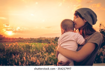 Young mother standing near a river & carrying her baby looking at the beautiful Sunset. Also Seeing a beautiful green field & mountain on a background. Mother kissing at her baby's head.