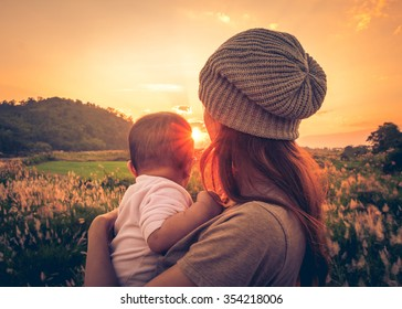 Young mother standing near a river & carrying her baby looking at the beautiful Sunset. Also Seeing a beautiful green field & mountain on a background.