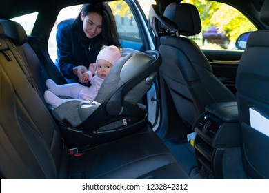 Young mother standing next to her baby sitting in baby seat backwards on backseat of the car with black interior