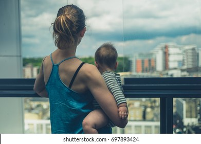 A young mother is standing on the balcony of her high rise apartment in the city holding her baby