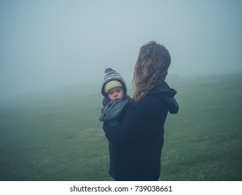 A young mother is standing on the moor in the mist with her baby