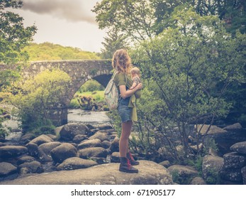 A young mother is standing in a river by an ancient bridge with her baby in a sling