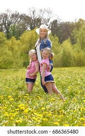 A young mother stands with her twin daughters  in a flower field.  The happy twins embrace their mother and enjoy the many flowers around them.