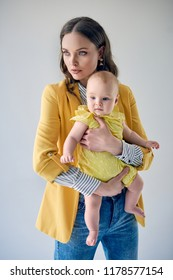 young mother in stylish outfit carrying adorable infant daughter and looking away isolated on grey