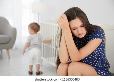 Young mother suffering from postnatal depression and little baby in room