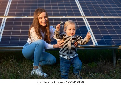 Young mother supporting her little son in making his first steps near solar panels, concept of modern family