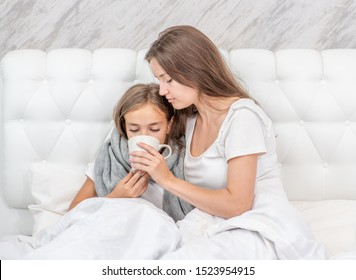 Young mother taking care of sick daughter in bedroom and giving her cup of tea