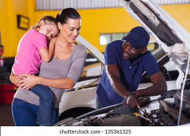 young mother taking her car for repair in garage with daughter sleeping on her shoulder