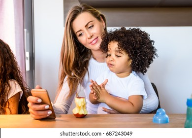 A young mother taking selfies with her small boy who is sitting in her lap at the kitchen table