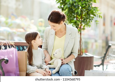 Young mother talking to cute daughter while playing together in the mall