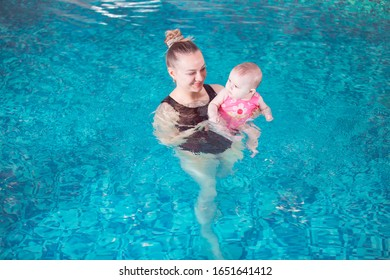 young mother teaches her child to swim