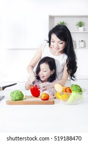 Young mother teaches her child making salad with vegetable in the kitchen
