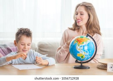 Young mother teaching her little son at home. Mom and her child studing geography indoors