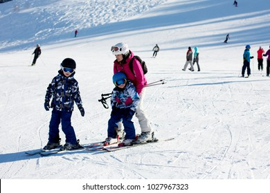 Young mother, teaching her preschool child to ski, sunny winter day in austrian Apls