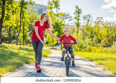 Young mother teaching her son how to ride a bicycle in the park.