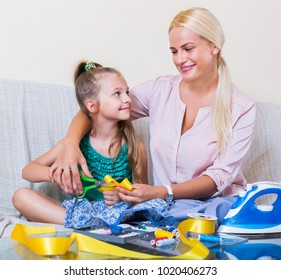 Young mother teaching little daughter to sew in home