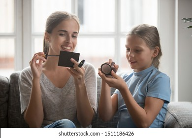 Young mother and teen daughter sit on couch have fun playing doing makeup at home together, smiling millennial sister or nanny spend enjoy weekend time with little girl having girlish beauty day