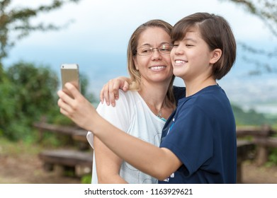 Young mother and teenage daughter taking a selfie in a very beautiful place outdoors (mixed race - Brazilian / Japanese). Background with light blue and green sky of trees.
