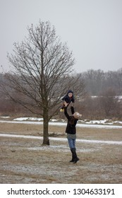 young mother throws her adorable little son above her head there is a tree in background
