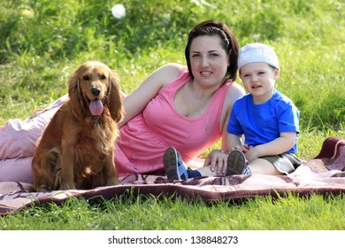 Young mother with toddler and dog sitting on rad on nature