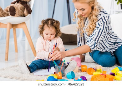 young mother and toddler drawing together at home