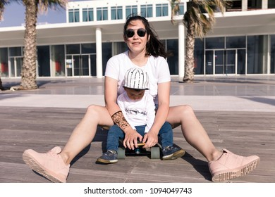 Young mother and toddler sitting on a skateboard at a beach boardwalk.