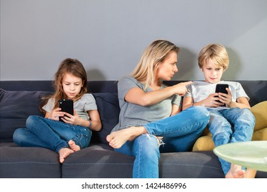 Young  mother trying to talk with her son while he is looking at smartphone ignoring her.Younger sister sitting next to them also looking at phone.. Family and modern technology addiction concept.