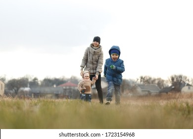 Young mother with two children, a little girl and a boy playing in the autumn field.