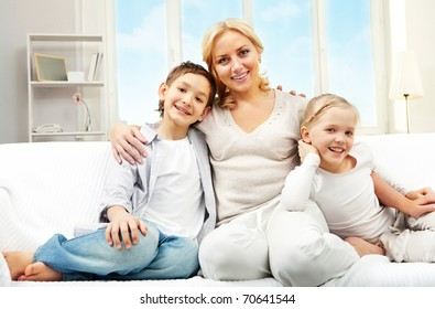 A young mother with two children sitting on sofa and smiling