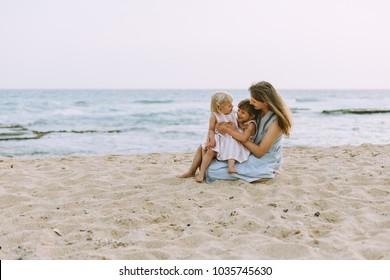 Young mother with two daughters on the beach