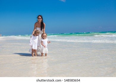 Young mother and two her fashion kids having fun at exotic beach on sunny day