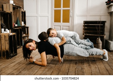 Young mother with two sons do the exercises