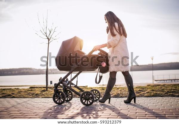 jonge moeder wandelen met baby, goed weer om te wandelen, gezonde levensstijl