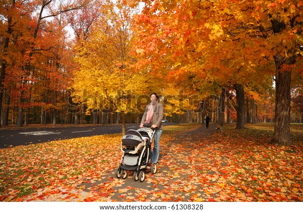 Young mother walking with baby in stroller in beautiful autumn park covered with red and yellow leaves.
