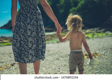 A young mother is walking hand in hand with her toddler on the beach on a sunny summer day