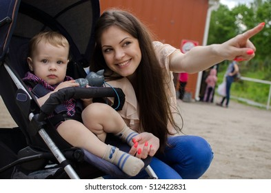 Young mother is walking with her small child in the park