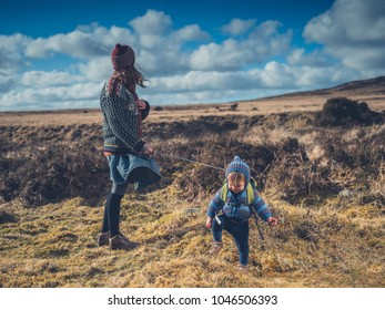 A young mother is walking on the moor with her little toddler in reins