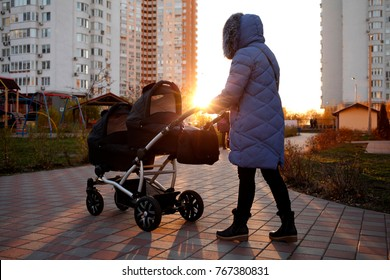 Young mother walking in a park with children in pushchair. Mom and kids in a buggy walk in forest. Woman pushing a double stroller for twin boy newborn baby. Active family outdoors.
