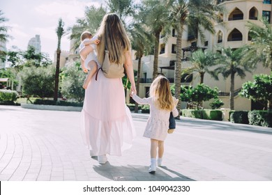 Young mother walking with two little daughters
