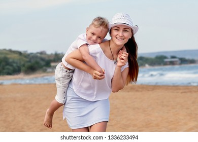 Young mother walks on beach with son. Portrait girl and child boy hugging, smiling. lifestyle, summer day. Carefree playing on outdoor sand,sea, joy, fun. concept of holiday, vacation