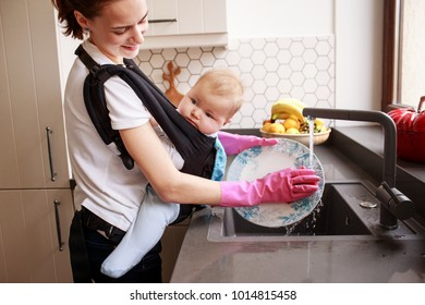 Young mother washing dishes with baby in ergo baby carrier backpack. Multifunctional concept