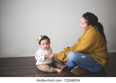 Young mother wearing fall sweater playing with her cute baby