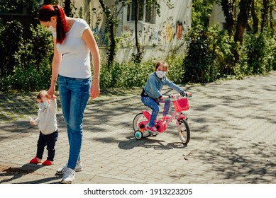 Young mother wearing a mask walking one daughter in a baby stroller and big sister on a bicycle outdoors during the pandemic year of 2021