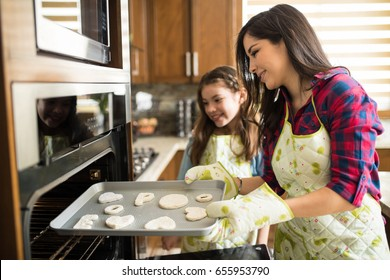Young mother wearing oven mitts and putting cookies in the oven with her daughter