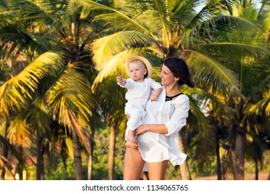 A young mother in a white shirt holds her little son in her arms and smiles at the background of tropical palm trees