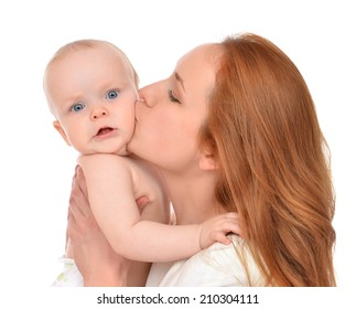 Young mother woman holding and kissing in her arms new born infant child baby kid girl in diaper on a white background