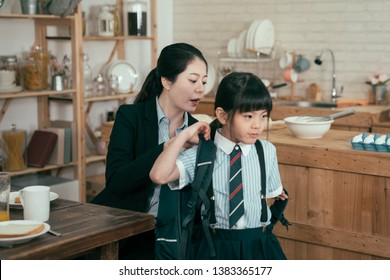 young mother worker in business suit help daughter get ready for school. Mom support child to wear backpack bag in wooden kitchen talking nag to little girl after breakfast time leaving home to study