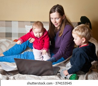 Young mother working with her baby at home with laptop
