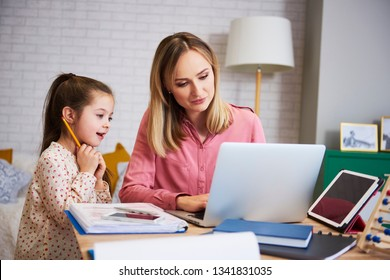 Young mother working from home with daughter